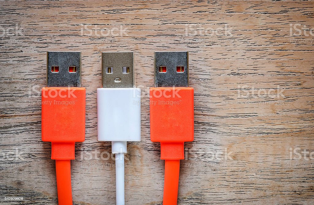 Orange and white USB cable Plug on wooden background. stock photo