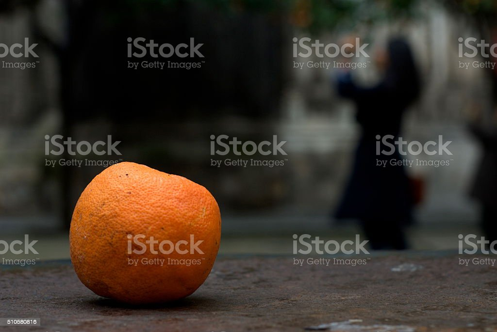 Orange and woman taking a picture stock photo