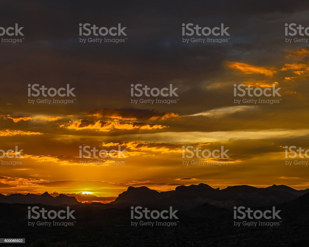 Orange Arizona sunset dramatic sunbeams mountains clouds and desert plants stock photo