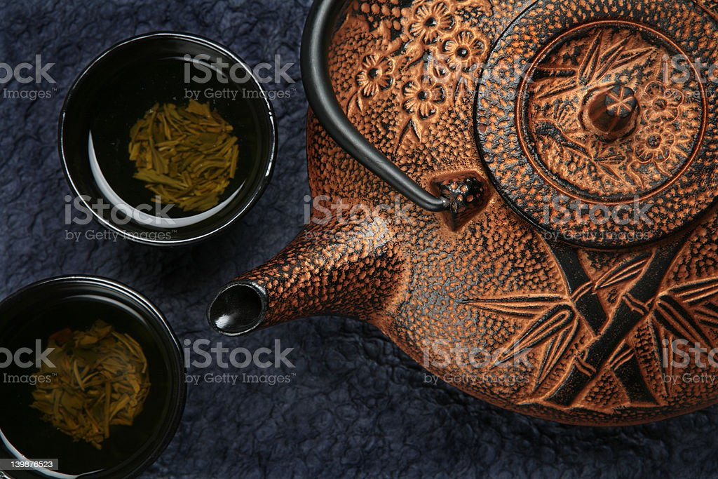 Orange asian teapot with cups and tea royalty-free stock photo