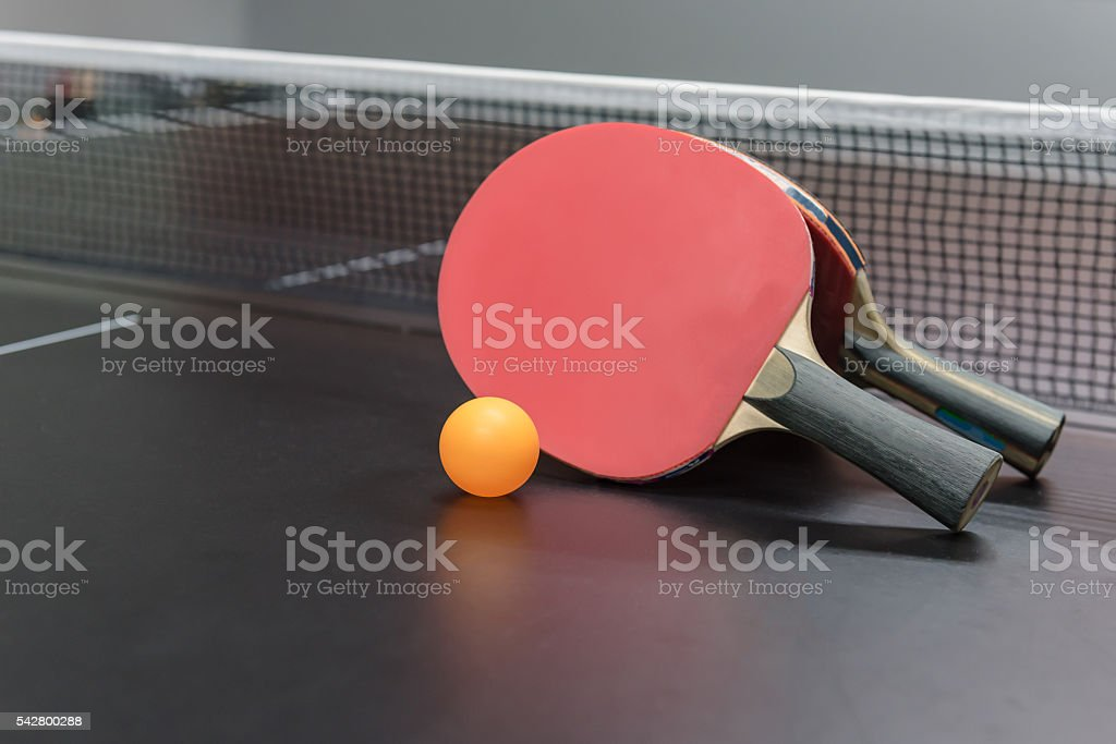 orange ball with red table tennis racket on black table stock photo