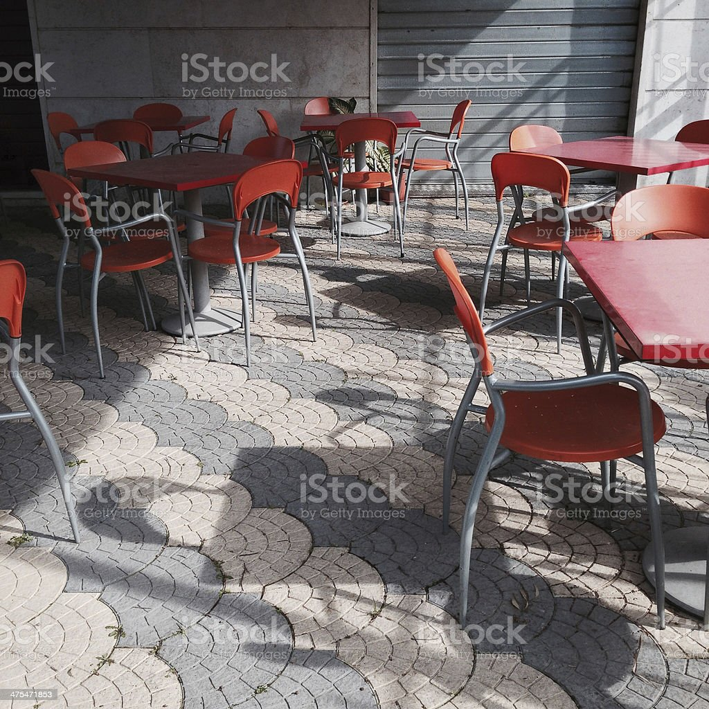orange bar tables, outdoors, with geometrical repetitive pattern on pavement stock photo