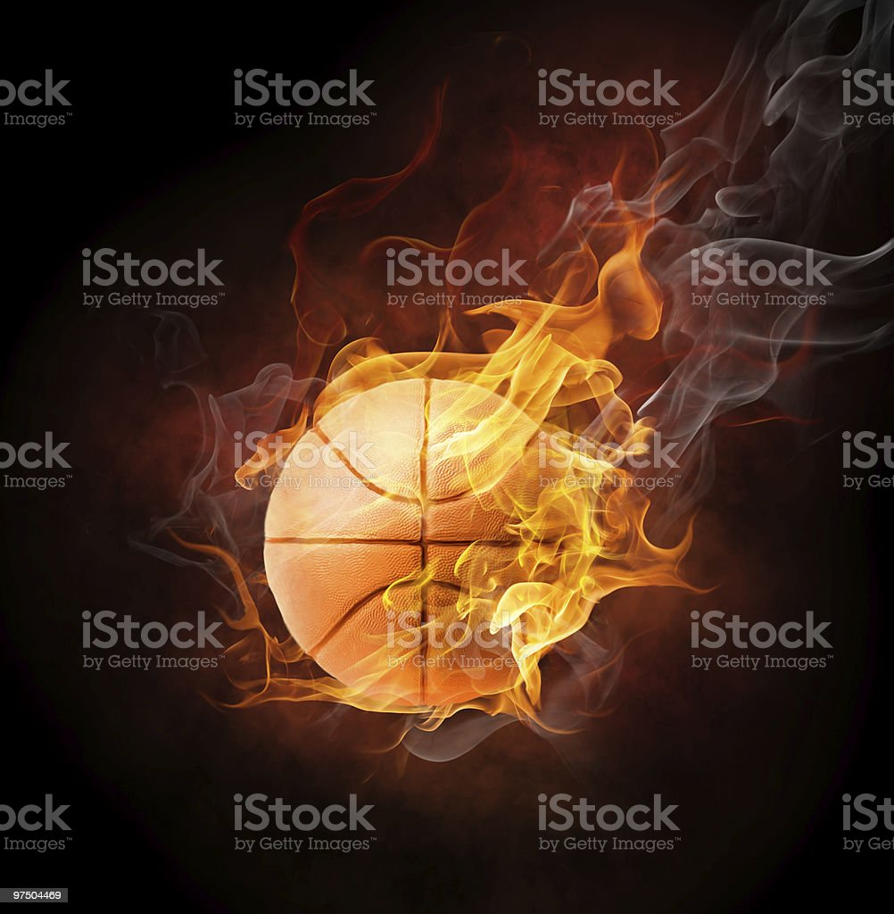 Orange basketball in smoky orange flames against black stock photo