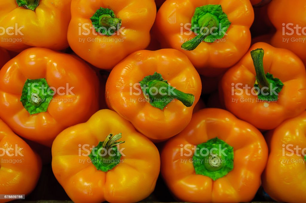 Orange bell peppers with green stalks forming a symmetrical display stock photo