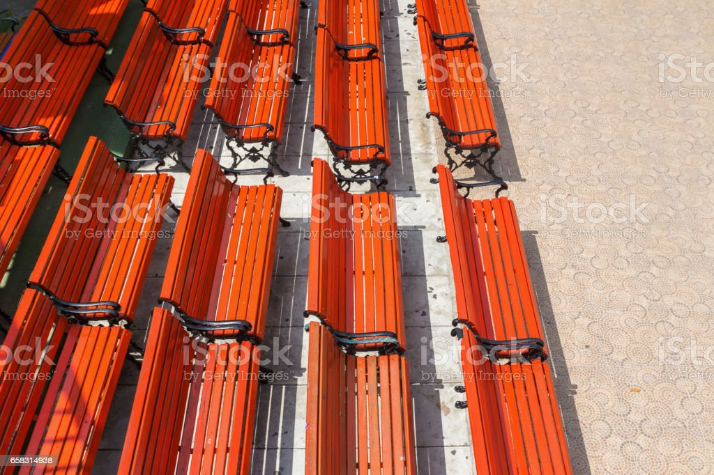 Orange bench laid lined, no people sitting, taken from high angle. stock photo