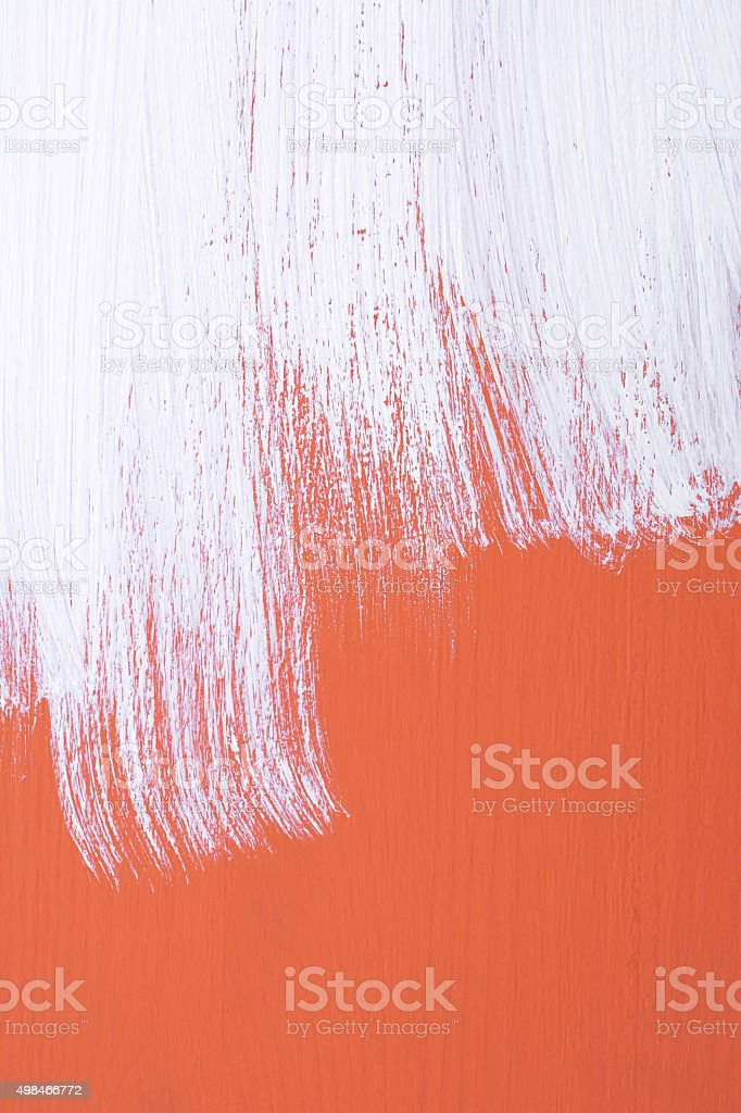 Orange board being roughly painted with white paint stock photo