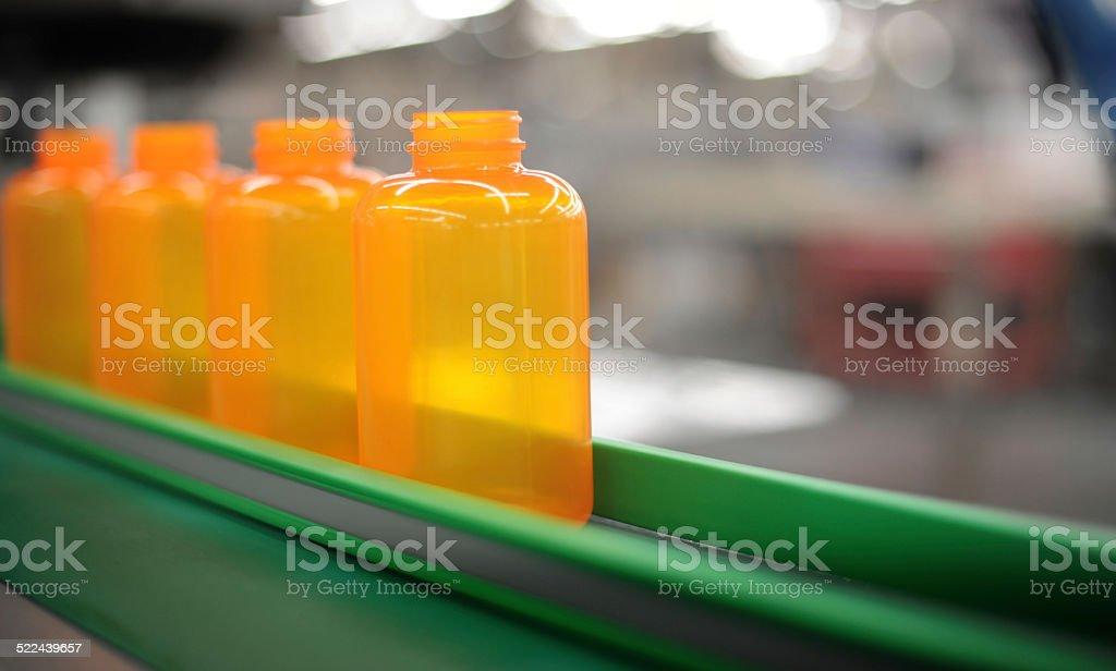 Orange bottles green conveyor stock photo