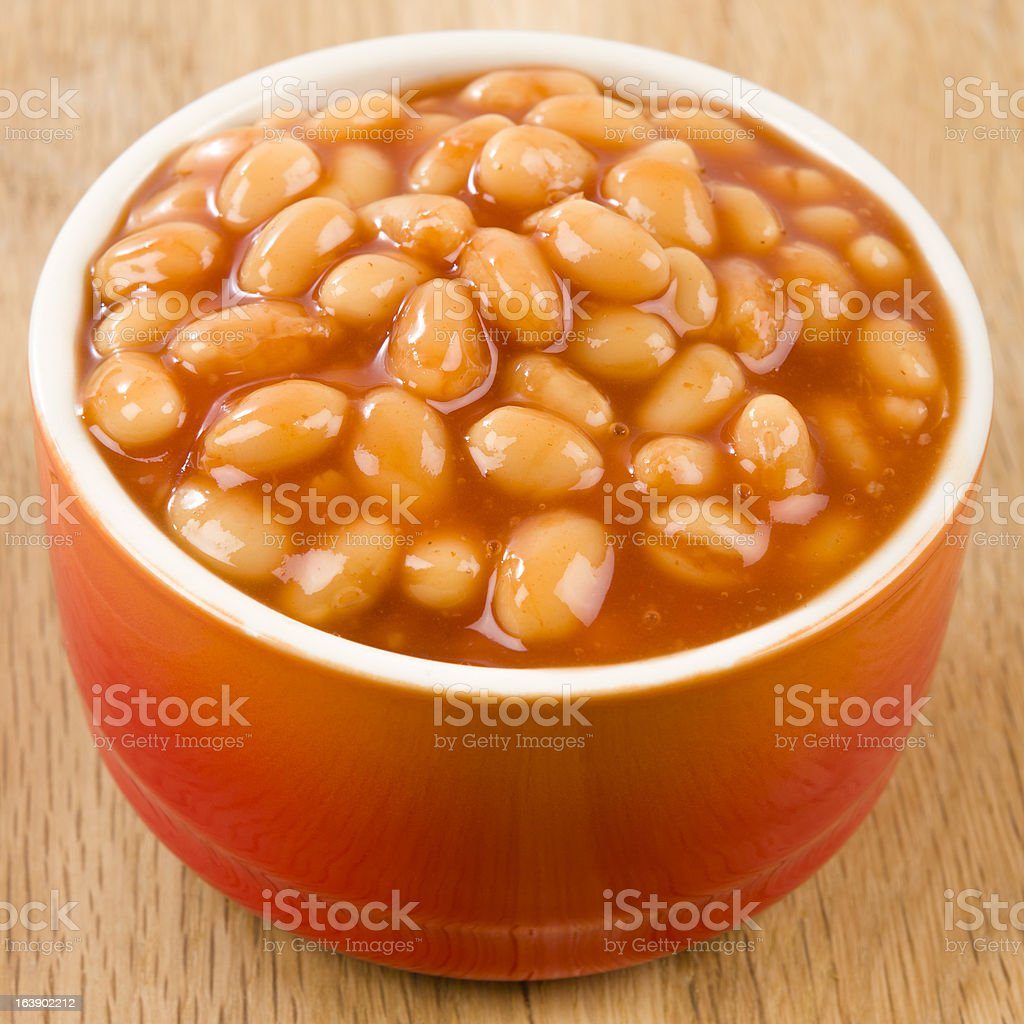 Orange bowl of baked beans on wooden table stock photo