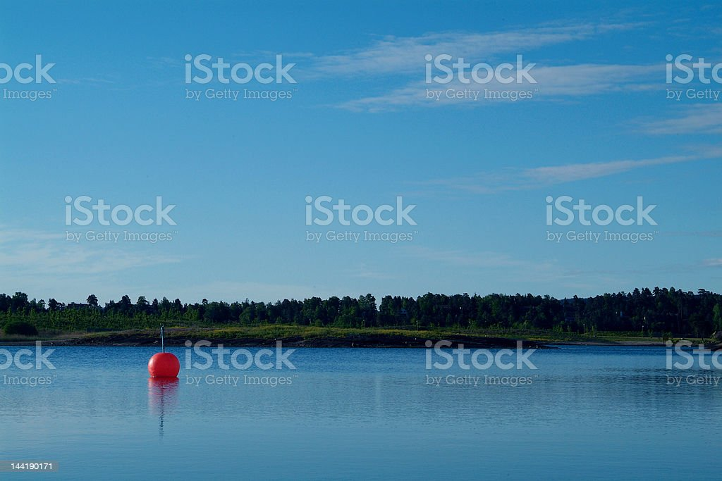 Orange buoy in calm waters royalty-free stock photo