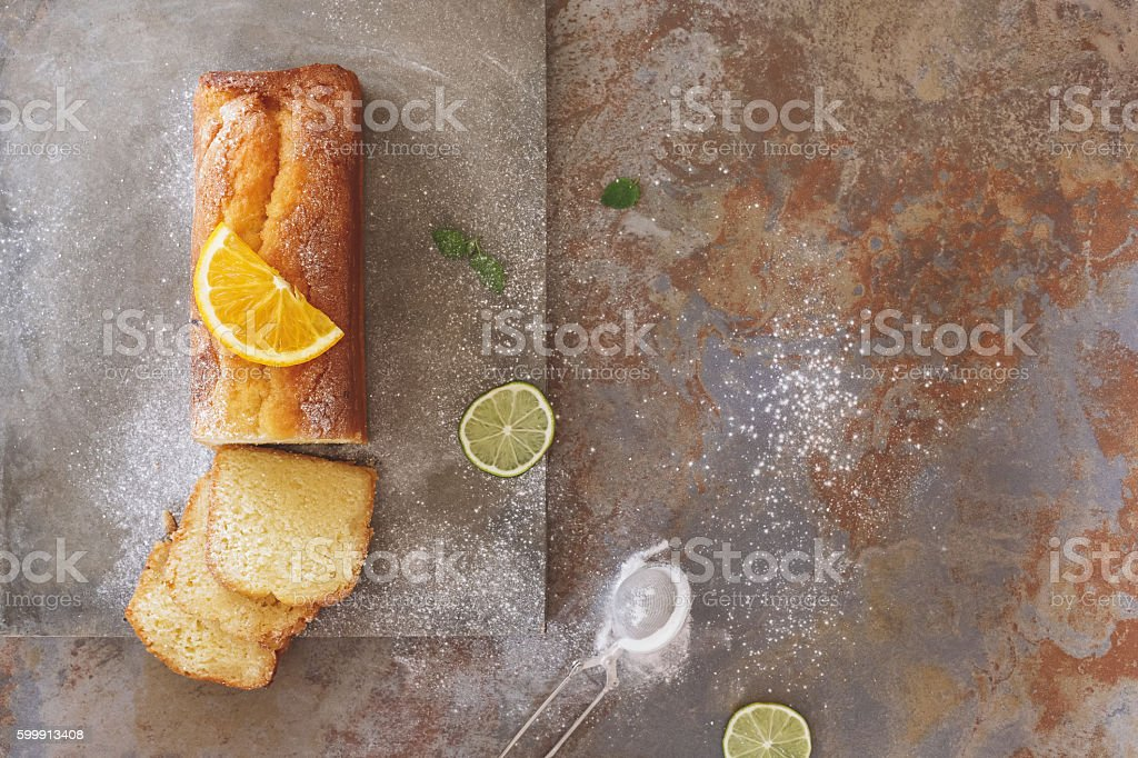 Orange cake drizzled with icing sugar, partly sliced stock photo