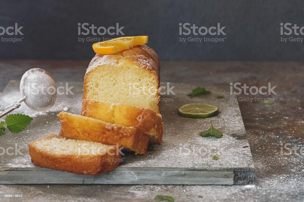 Orange cake partly sliced and fresh fruits stock photo