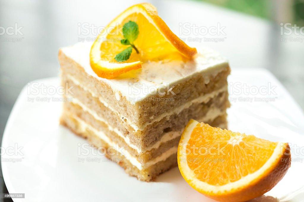 Orange cake slice on the plate with fresh orange slice. stock photo