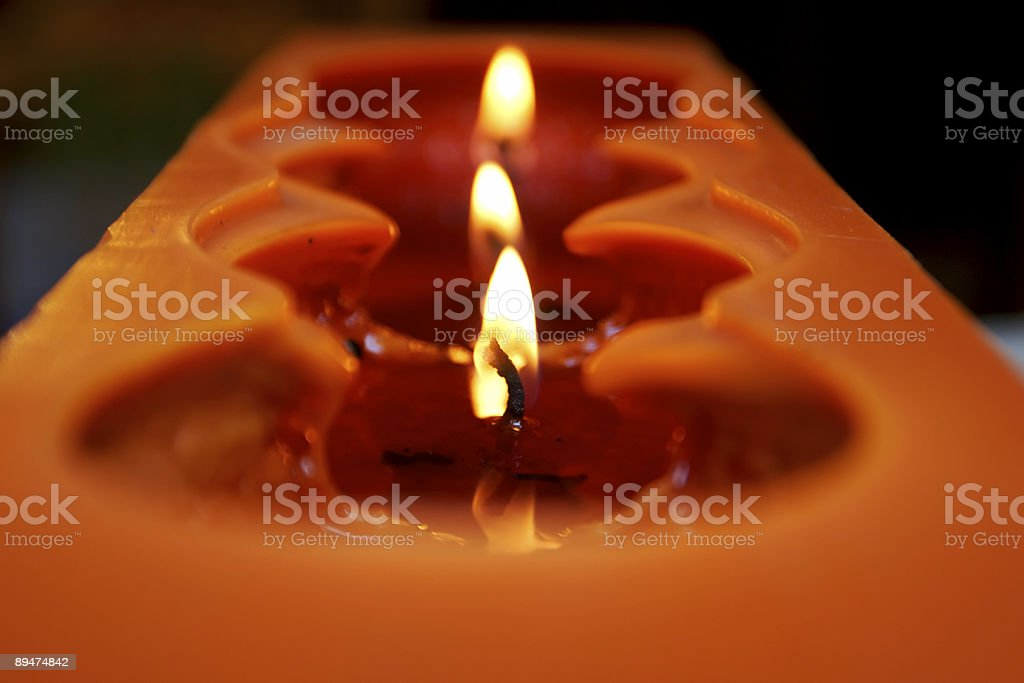 Orange candle with 3 wicks royalty-free stock photo