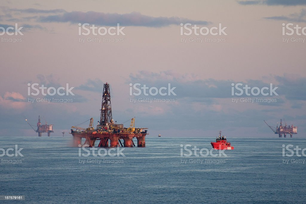 Orange cargo ship approaching an oil rig at sea stock photo