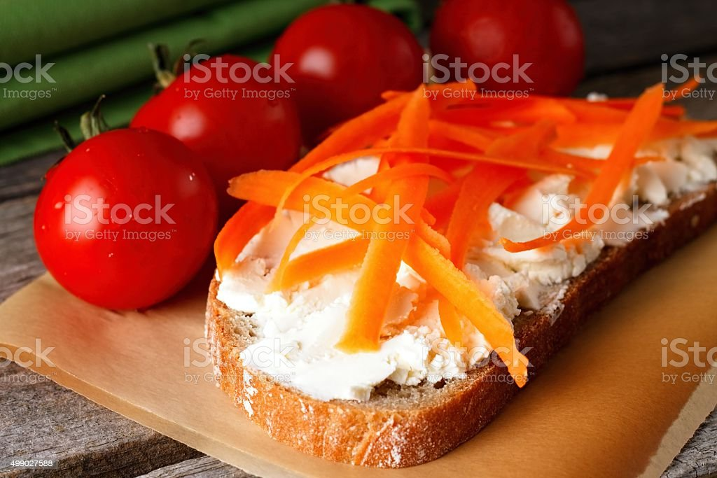 Orange carrot shaves on bread with curd cheese stock photo