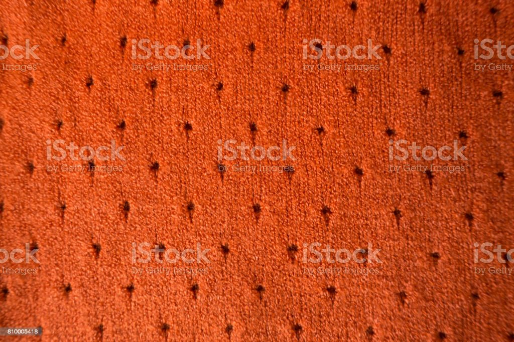 Orange cashmere stockinette fabric with perforated dots stock photo