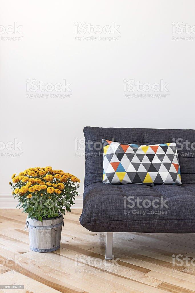 Orange chrysanthemums and sofa with bright cushion stock photo
