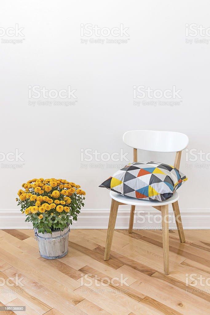 Orange chrysanthemums bright cushion on a chair royalty-free stock photo