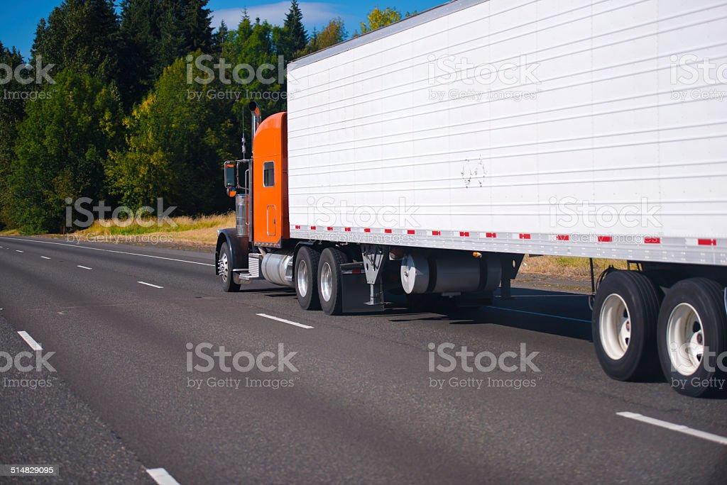 Orange classic semi truck and trailer on highway stock photo