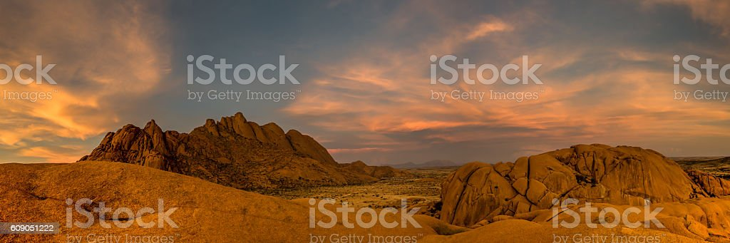 orange clouds above granite hills in a panorama shot. stock photo