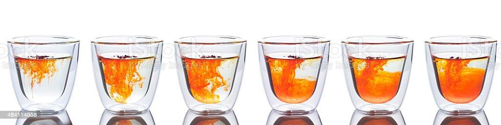 orange color spread in glass of water stock photo