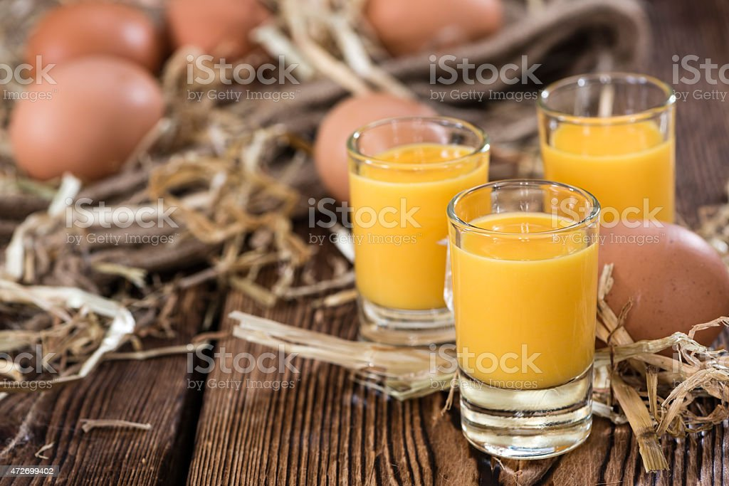 Orange colored drink in small glasses on table with eggs stock photo