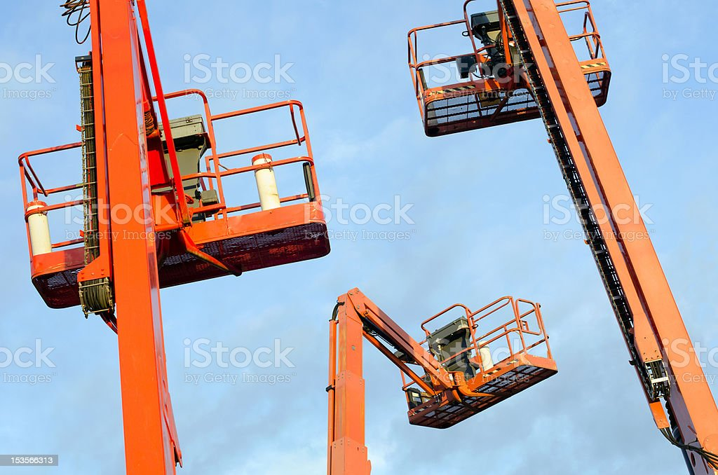 Orange construction crane baskets against blue sky stock photo