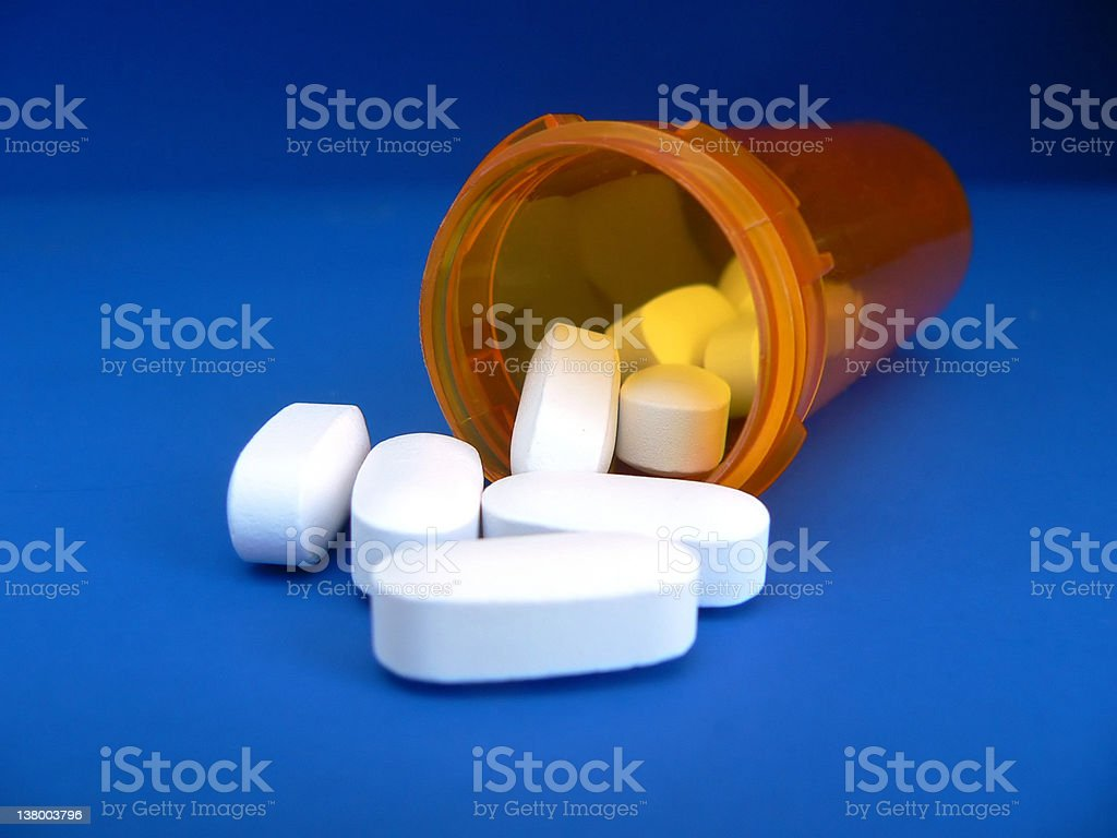 A orange container with pills spilling out of it royalty-free stock photo