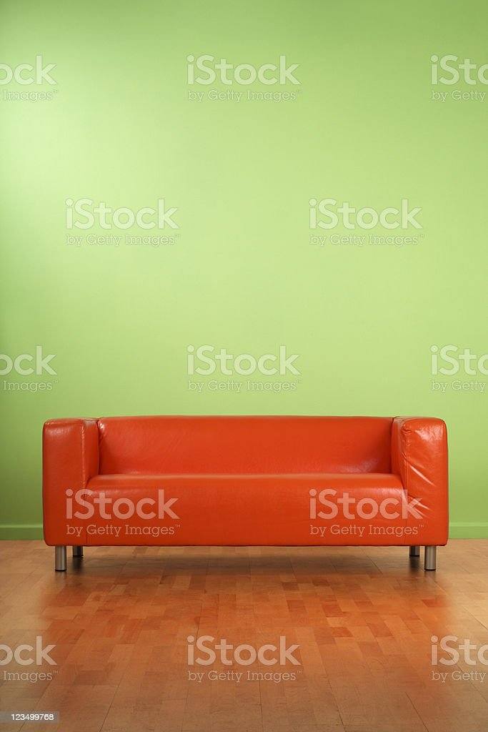 Orange Couch on a Green Wall royalty-free stock photo