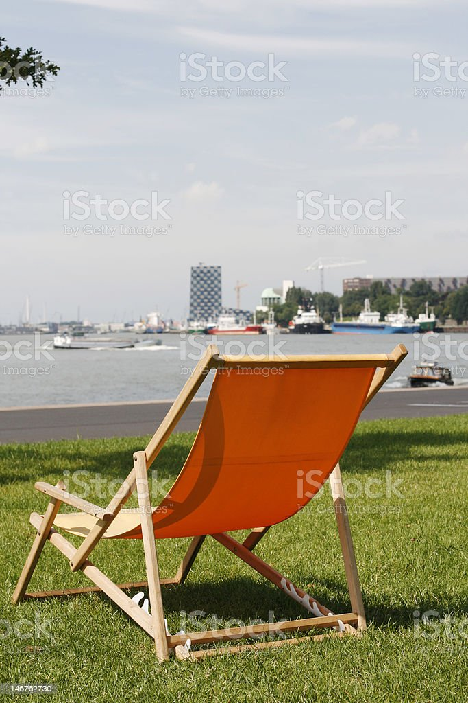 Orange deckchair in grass with view on busy river royalty-free stock photo