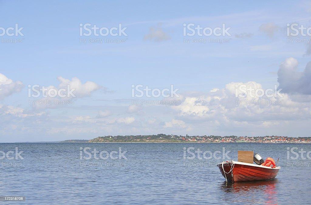 Orange dinghy i a blue world stock photo