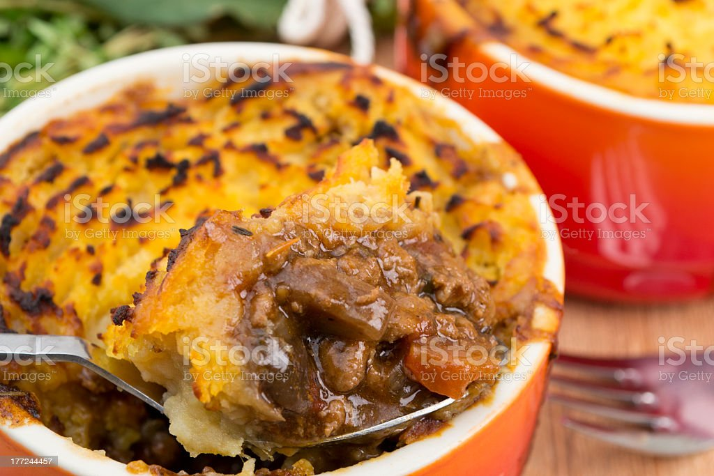 Orange dish of cottage pie being served with a large spoon stock photo