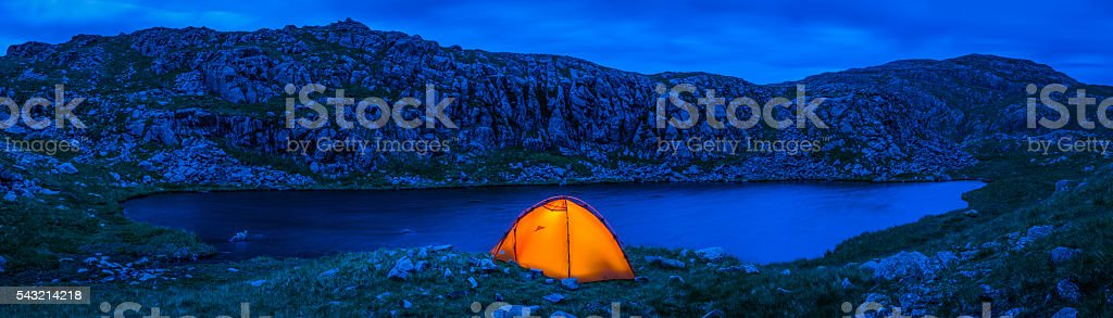 Orange dome tent camping beside remote mountain lake wilderness panorama stock photo