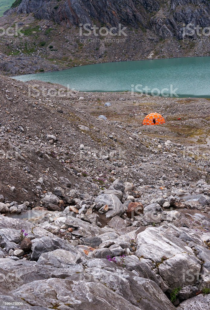 Orange domed tent in rocky glacial valley stock photo