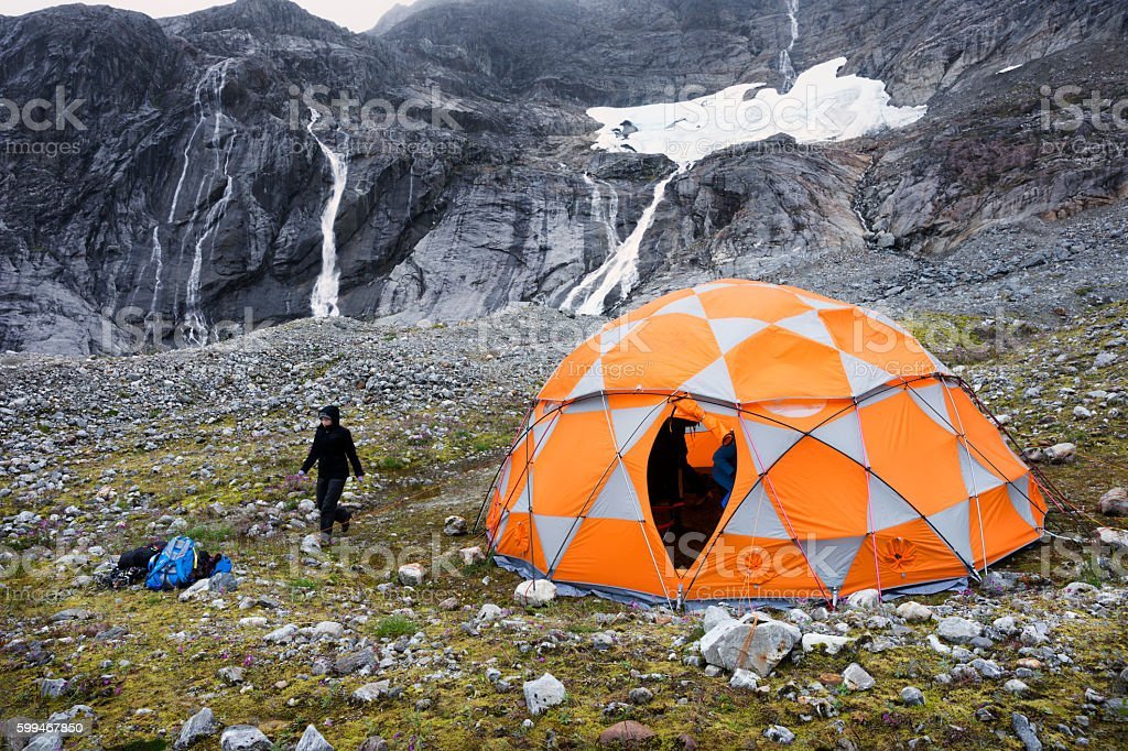 Orange domed tent near waterfall on glacier stock photo