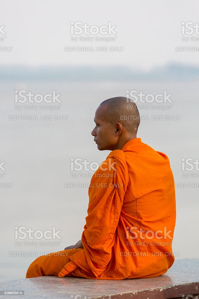 Orange dressed Cambodian monk looking at the Mekong, Phnom Penh stock photo
