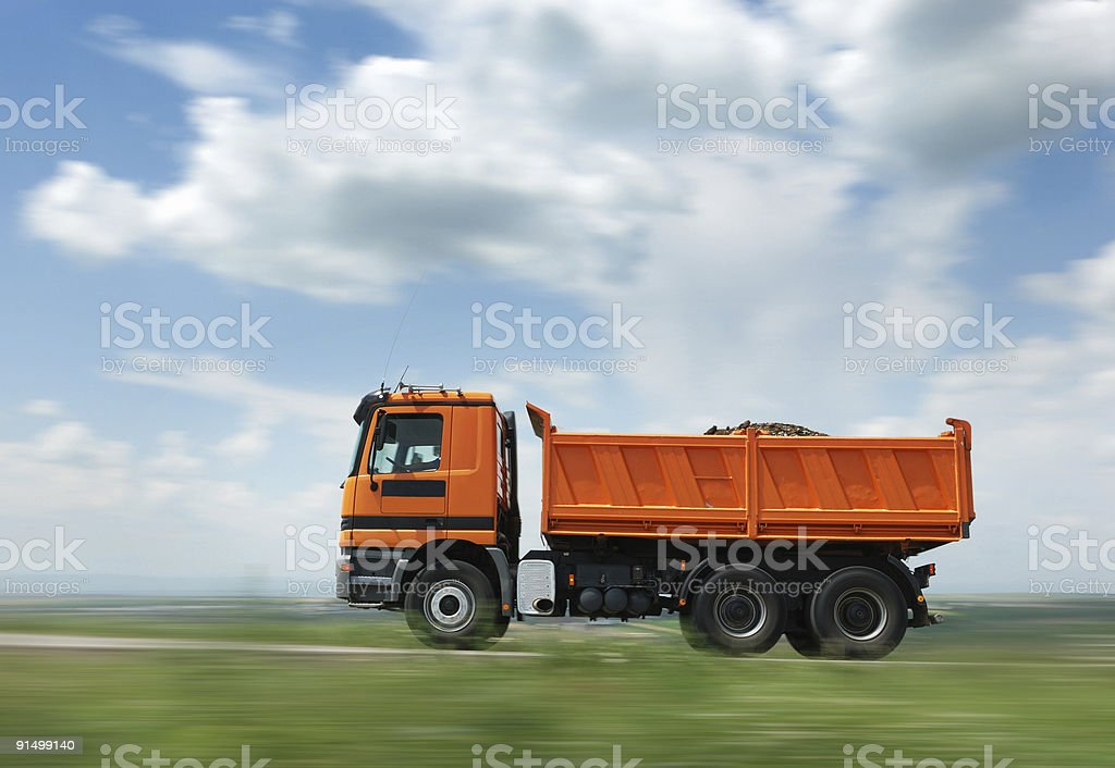 Orange dump truck in motion on the road royalty-free stock photo