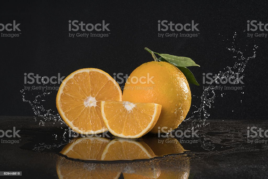 orange duo with Leafs  water splash black background. stock photo