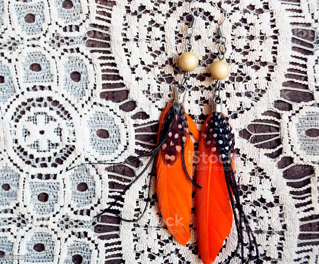 Orange earrings from feather on lace background stock photo