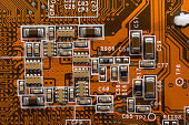 orange electronic circuit board close up.