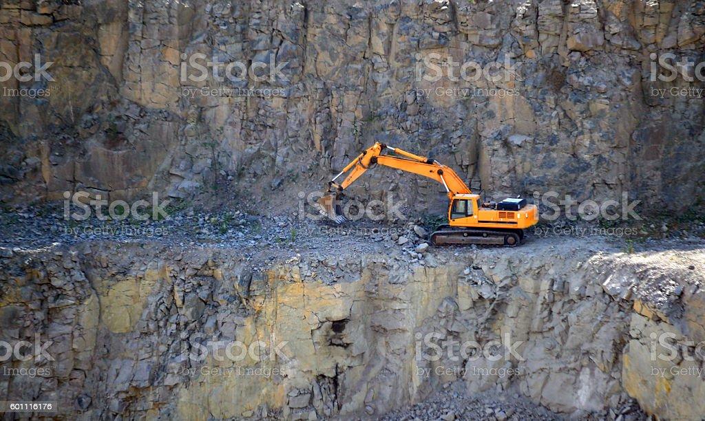 Orange excavator, digger in a granite quarry stock photo