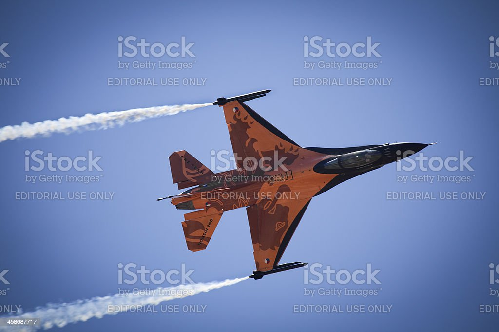 Orange F16 fighter jet against blue sky. royalty-free stock photo