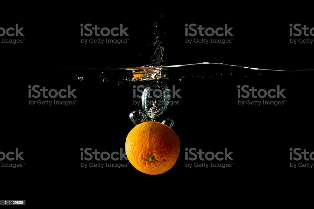 Orange falling in water on black background stock photo