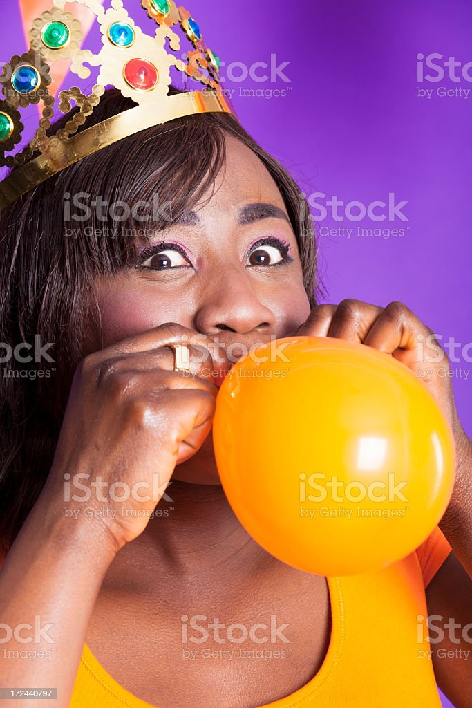 Orange fan blowing up a balloon royalty-free stock photo
