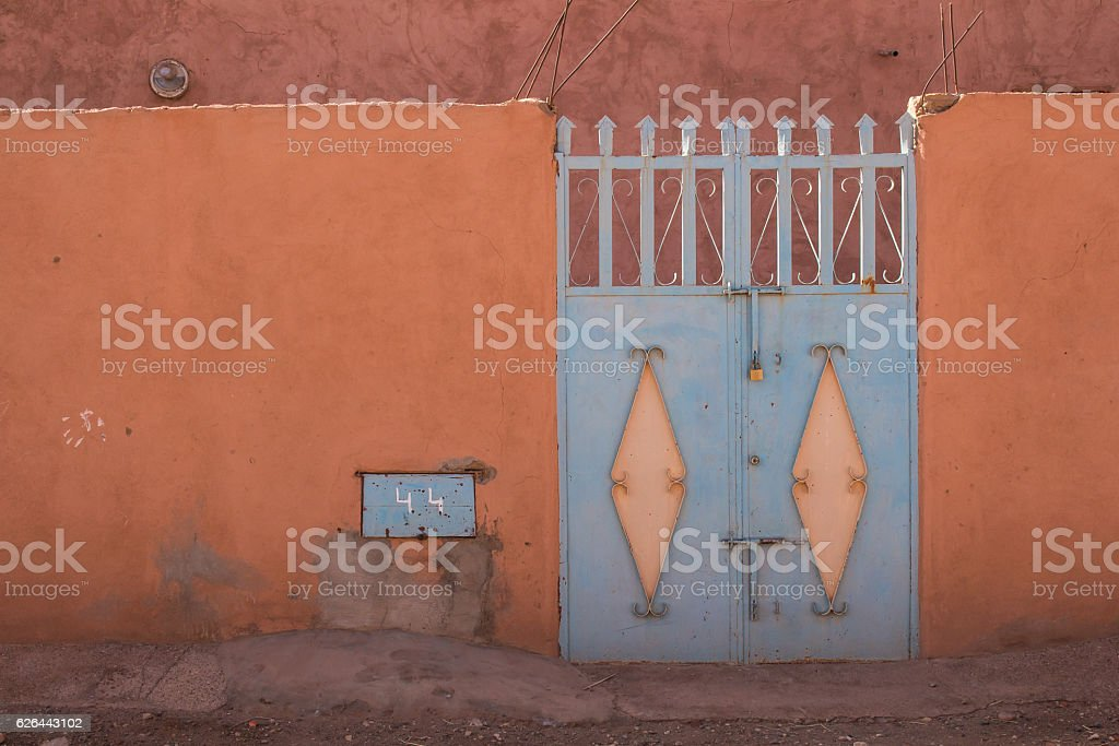 Orange fence and a blue gate, Morocco stock photo
