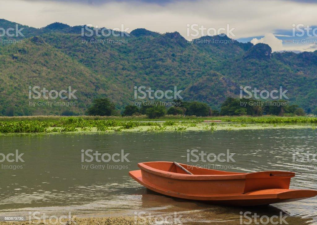 Orange fiberglass boat floats in a river stock photo