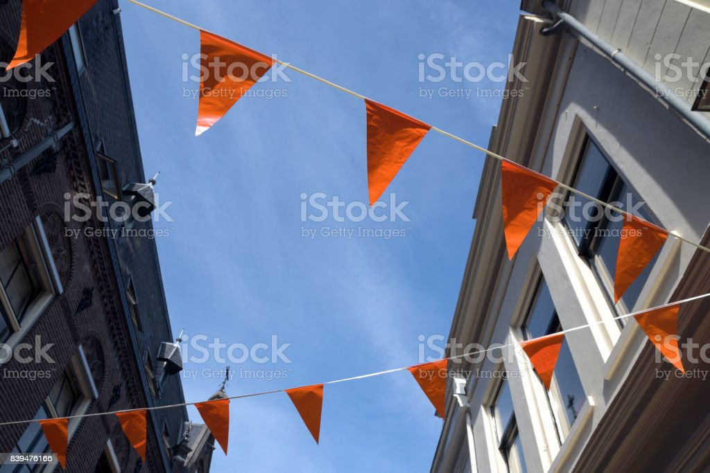 Orange flags in a Dutch city, decoration to support the soccer team or celebrate the queens day in the Netherlands stock photo