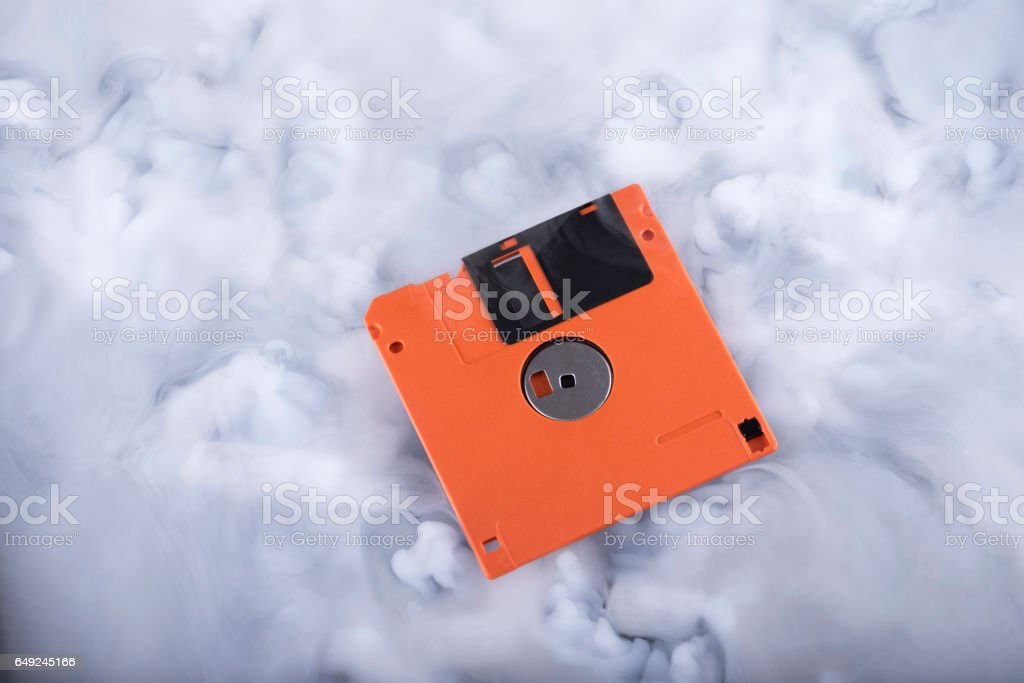 Orange floppy disk in the clouds stock photo