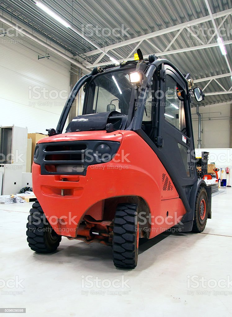 Orange forklift loader in the modern warehouse. stock photo