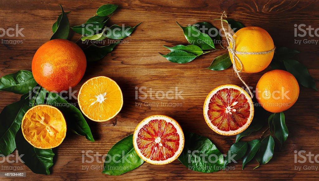 Orange fruit among green leaves on wooden table stock photo